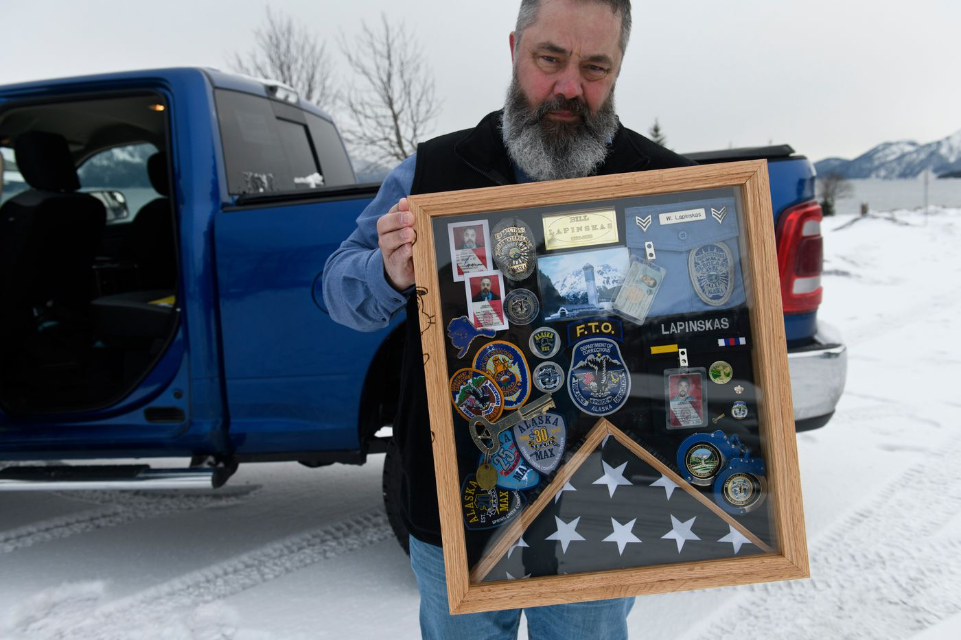 Former Spring Creek Correctional Center superintendent Bill Lapinskas holds a shadow box made for him as a gift by Spring Creek staff and prisoners. (Marc Lester / ADN)