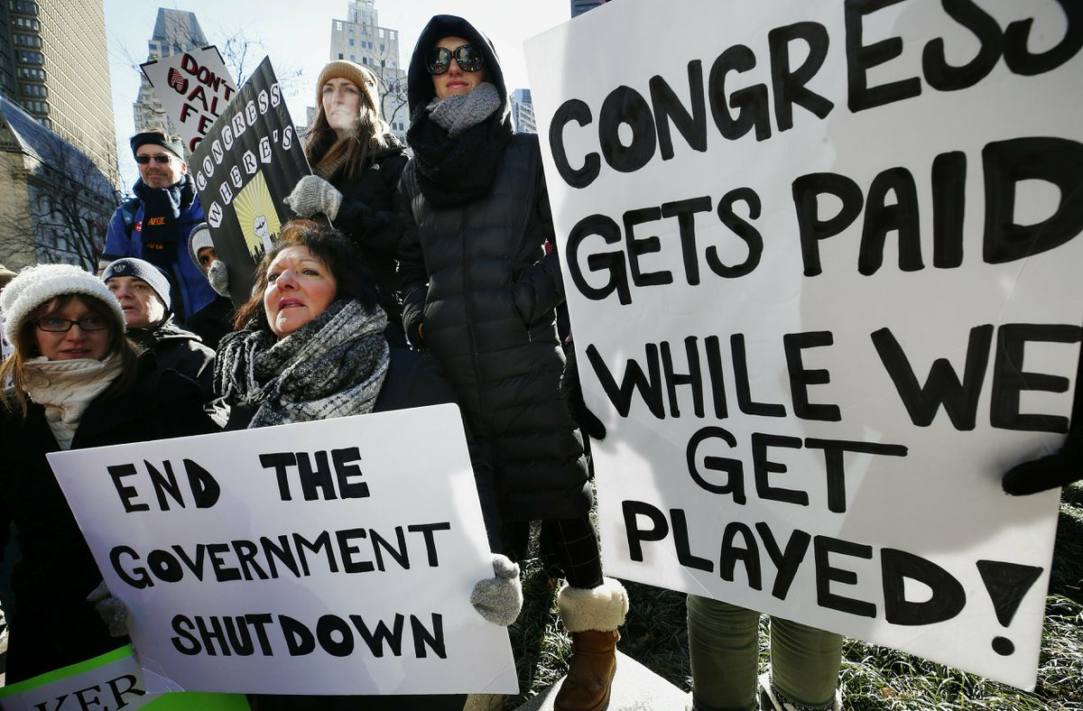 Government workers and their supporters hold signs during a protest in Boston, Friday, Jan.11, 2019. The workers rallied with Democratic U.S. Sen. Ed Markey and other supporters to urge that the Republican president put an end to the shutdown so they can get back to work. (AP Photo/Michael Dwyer)