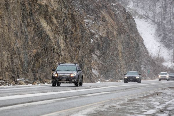 Snow falls on motorists driving northbound on the Seward Highway south of Beluga Point on Turnagain Arm Wednesday, Feb. 20, 2019. (Loren Holmes / ADN)