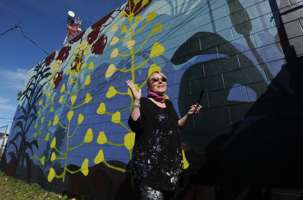 Artist Linda Infante Lyons is painting a 100-foot by 14-foot mural on the side of Praise Temple that borders the Government Hill Commons and community orchard.  (Bill Roth / ADN)