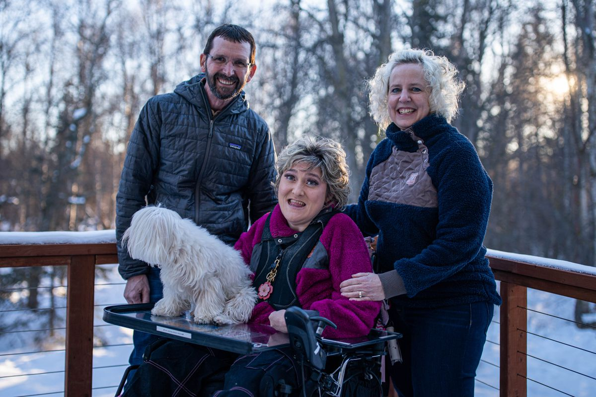 Mark Huber and Cindy Mittlestadt, with their daughter Tricia Huber and dog Starbuck, photographed at their home on Friday in South Anchorage. Huber and Mittlestadt were already vaccinated as caregivers of their 34-year-old daughter, who has cerebral palsy and other developmental disorders, but they struggled to get an appointment for Tricia, who is too young under state guidelines despite her health issues. Tricia finally received her first shot last Saturday. (Loren Holmes / ADN)