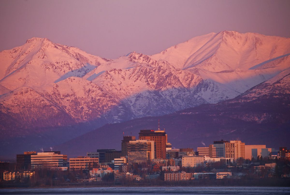 The sun sets on Downtown Anchorage, casting pink and purple hues on the city and mountain range behind it, on Nov. 3, 2020. The sun set at 4:50 p.m., about 20 minutes after this photo was taken. (Emily Mesner / ADN)