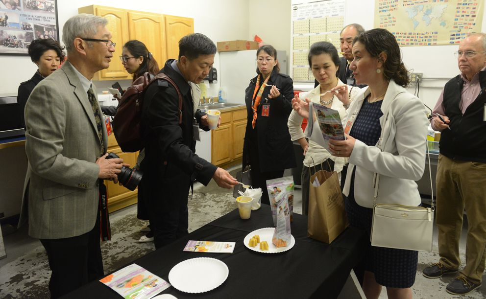 Zoi Maroudas, at right, provides a delegation from the World Trade Center in Harbin, China, a sample of the halibut variety of Bambino's Frozen Baby Food after a tour of the Copper River Seafoods plant. (Bob Hallinen / ADN)