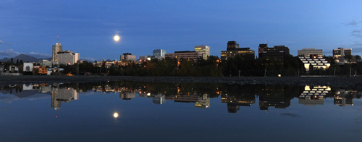 The moon rises over the Anchorage, AK skyline and is reflected in a puddle near the small boat launch next to Ship Creek on Tuesday, September 13, 2016. (Bob Hallinen / ADN)