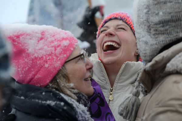 Tiffany Hall, a speaker at the the Women's March on Anchorage rally, laughs after getting a hug from Sheila Selkregg. The march drew women, men and children to the Delaney Park Strip on a snowy Saturday, Jan. 21, 2017. (Anne Raup / Alaska Dispatch News)