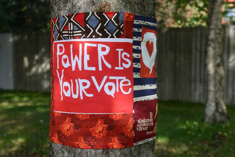 """Fabric art on trees states """"Power is Your Vote"""" and a smattering of African proverbs on Friday, September 9, 2016, along West Northern Lights Boulevard in Turnagain. (Erik Hill / Alaska Dispatch News)"""