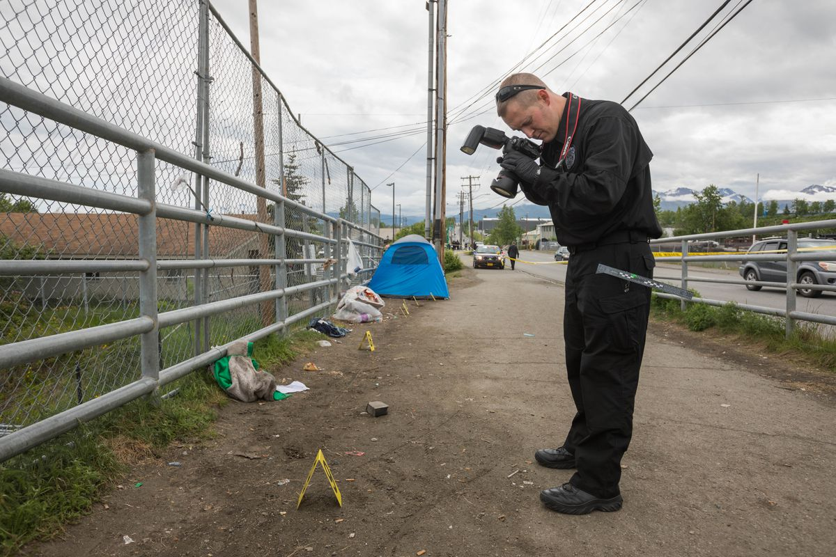 Anchorage police officer Bryan Ranger photographs the scene of a fatal stabbing Thursday. The stabbing occurred near the corner of Third Avenue and Karluk Street just before 8 a.m. (Loren Holmes / Alaska Dispatch News)