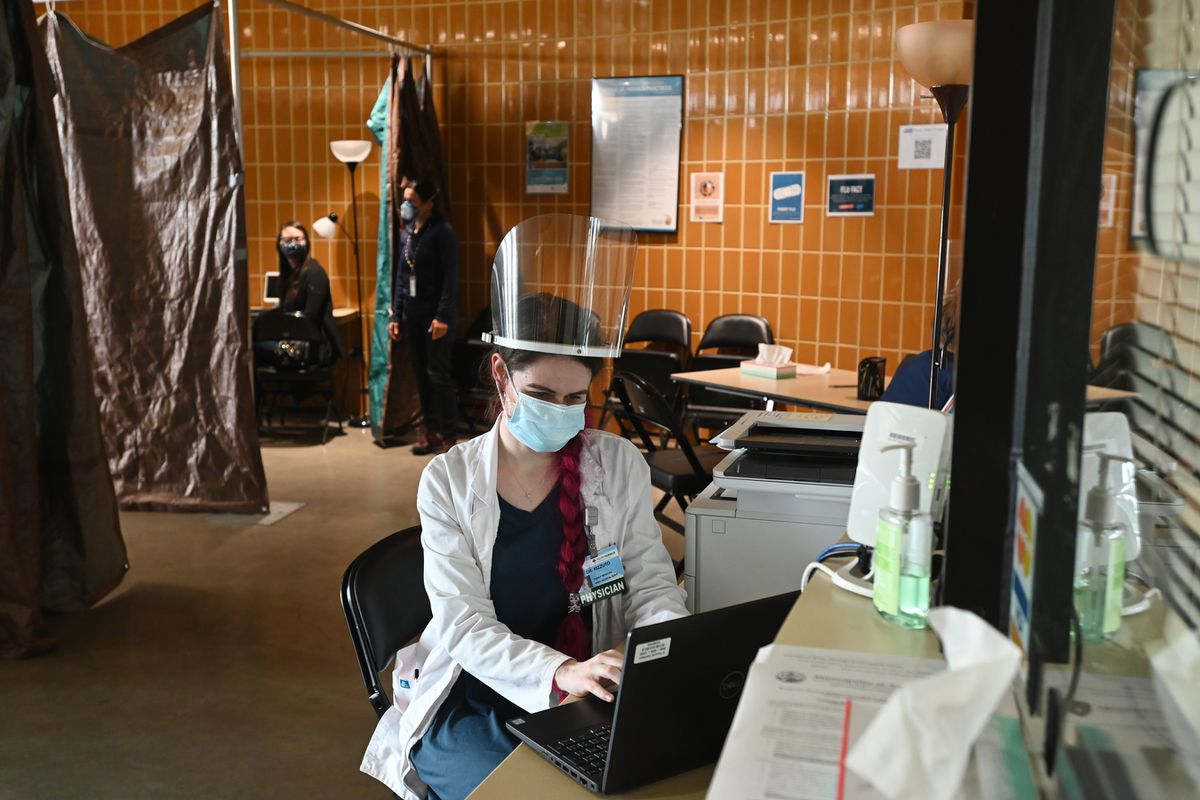 Dr. Alyssa Rizzuto, supervising physician from Providence Alaska Medical Center, reviews charts at the clinic inside Sullivan Arena on Monday, Sept. 14, 2020, which is operating as a mass shelter for the Anchorage homeless population. (Bill Roth / ADN)