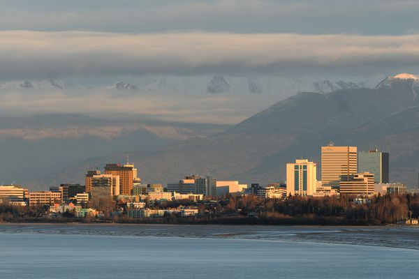 Late-afternoon sunshine splashes across downtown Anchorage as layered clouds obscure the Chugach Mountains on Wednesday, Nov. 16, 2016, in a view from west Anchorage. (Erik Hill / Alaska Dispatch News)