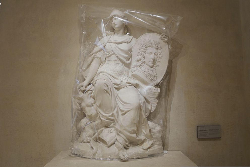 The sculpture called 'Funerary monument to Francois-Louis de Bourbon, Prince de Conti' by French sculptor Nicolas Coustou is covered with plastic sheeting, at the Louvre museum in Paris, Thursday, Feb. 11, 2021. (AP Photo/Thibault Camus)