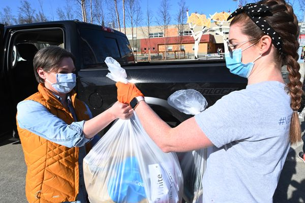 Traci Thompson, left, picked up belongings for her daughter and two other students from teacher Kirstin Barboza at Sand Lake Elementary on Tuesday, May 5, 2020, during the COVID-19 pandemic. (Bill Roth / ADN)