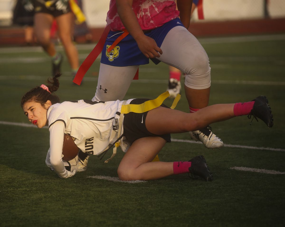 South's Gracie Hoover (25) falls to the ground after attempting to dodge Bartlett defenders during Thursday's flag football game at South High School. (Emily Mesner / ADN)