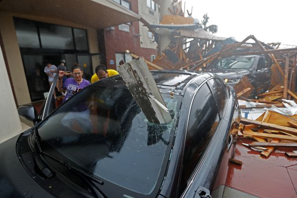 A woman checks on her vehicle as Hurricane Michael passes through, after the hotel canopy had just collapsed, in Panama City Beach, Fla., Wednesday, Oct. 10, 2018. (AP Photo/Gerald Herbert)