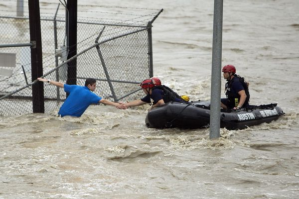 Rescue personnel grab the the hand of a man stranded in rushing water at the northwest corner of Lamar Blvd. and 15th St. in Austin, Texas. Shoal Creek overflowed its banks and inundated the major traffic artery with rushing water. Several cars were stalled under and near the 15th St. bridge Monday, May 25, 2015.