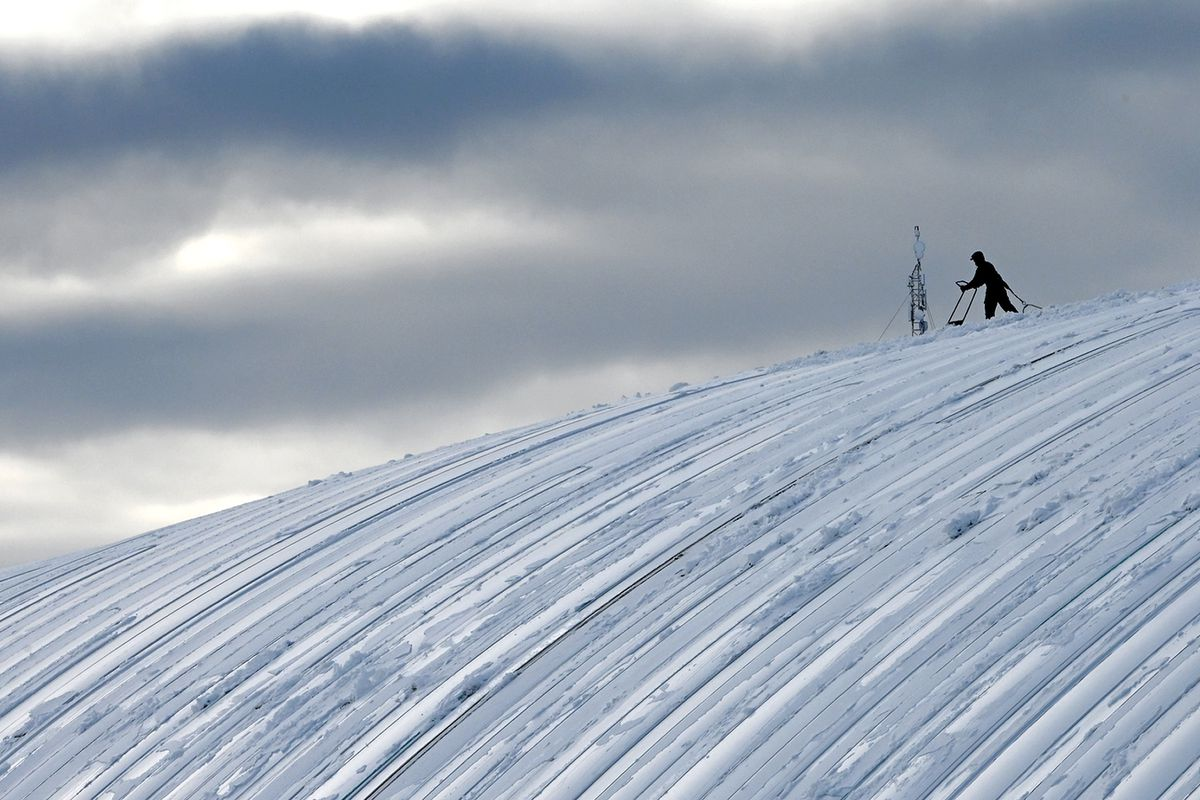 Scott Ezell with Chinook Roofing shovels the recent snowfall from the roof of The Dome on Wednesday, Feb. 19, 2020. (Bill Roth / ADN)