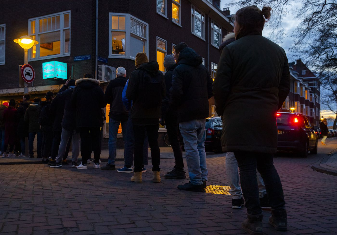 People queue to buy marijuana at the coffeeshop Bulwackie in Amsterdam, Netherlands, Sunday, March 15, 2020, after a TV address by health minister Bruno Bruins who ordered all Dutch schools, cafes, restaurants, coffeeshops and sport clubs to be closed on Sunday as the government sought to prevent the further spread of coronavirus in the Netherlands. (AP Photo/Peter Dejong)