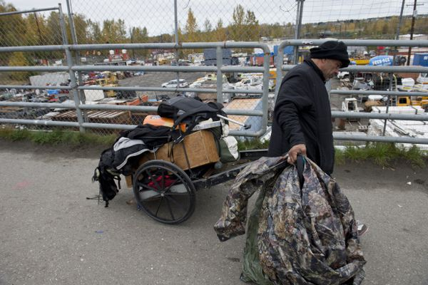 A man moves his belongings on Third Avenue. Members of the Anchorage Police Department direct a cleanup along Third Avenue and Barrow Street where many homeless people had been staying on Sept. 27, 2017. (Marc Lester / Alaska Dispatch News)