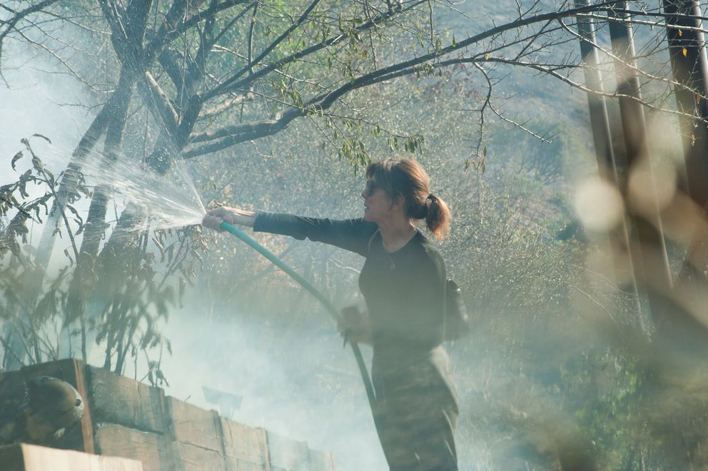 Elizabeth Rawjee sprays water Thursday onto hotspots left by the Skirball fire in her backyard on the west side of Los Angeles. REUTERS/Andrew Cullen