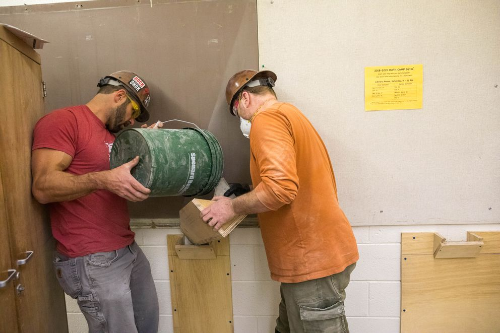 Adam Breitinger, left, and Justin Pedersen, with Roger Hickel Contracting, pour grout into a hollow wall to reinforce it on Friday at East High. The work had been planned before the Nov. 30 earthquake, and will make the structure stronger. (Loren Holmes / ADN)