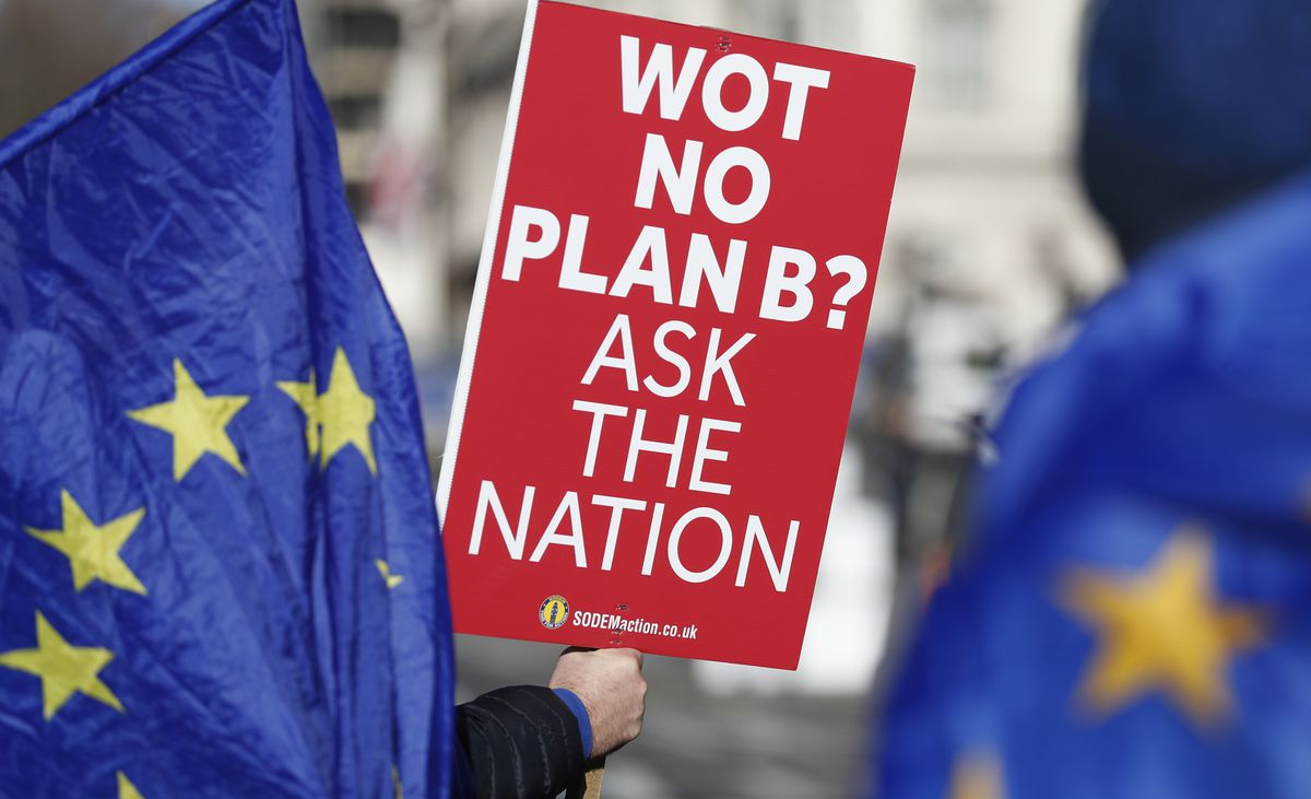 Anti Brexit protester Steve Bray who is almost permanently demonstrating outside the Houses of Parliament watches the traffic as he holds up placards in London, Monday, Jan. 28, 2019. (AP Photo/Alastair Grant)