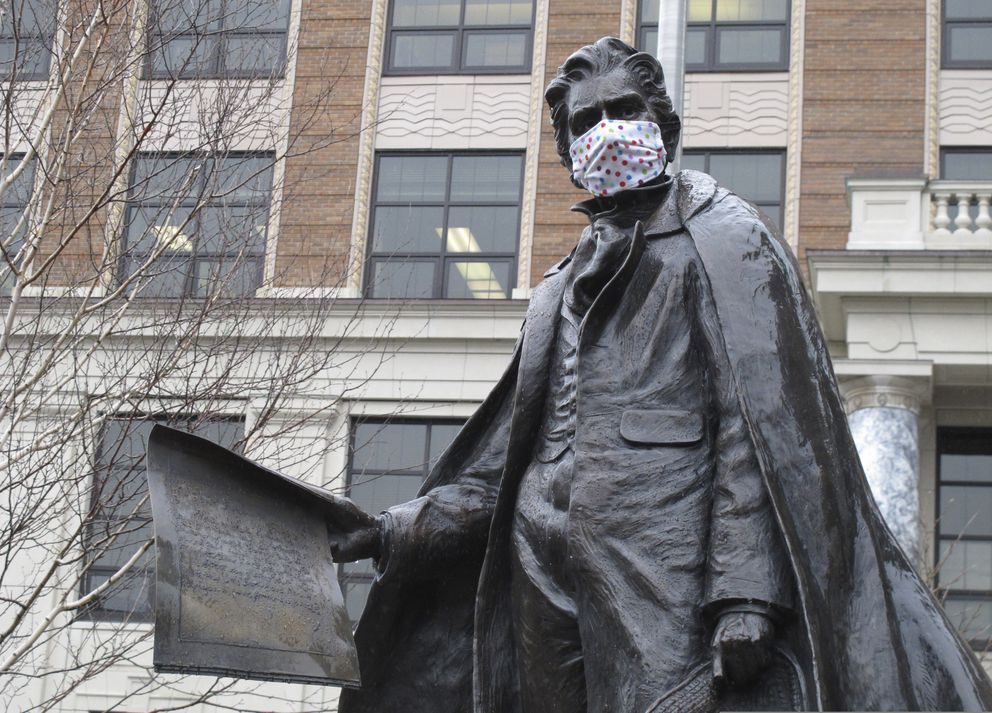 A statue of William Seward near the Alaska Capitol is shown outfitted with a mask on Friday, April 24, 2020, in Juneau. (AP Photo/Becky Bohrer)