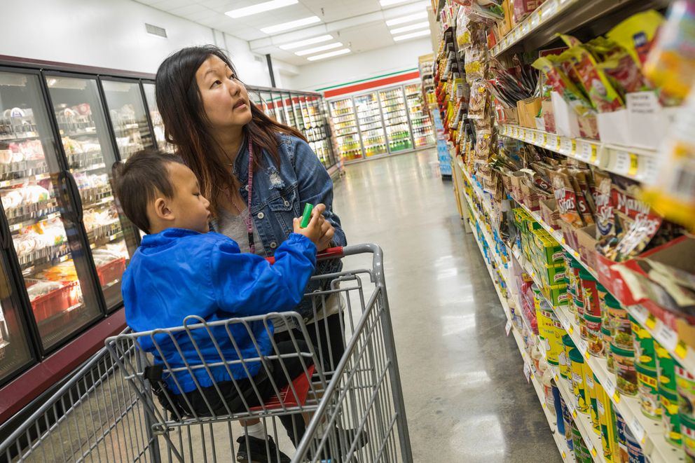 Kalia Xiong, with her son Kezekiel Chang, 2, shops for ingredients for a red curry Tuesday at the Red Apple supermarket in Mountain View. (Loren Holmes / Alaska Dispatch News)