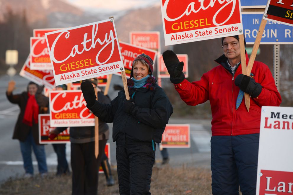 Republican incumbent Cathy Giessel campaigns to retain her state Senate seat along Tudor Road on Tuesday afternoon, November 4, 2014, at Baxter Road. Husband Rich helps greet motorists at right.