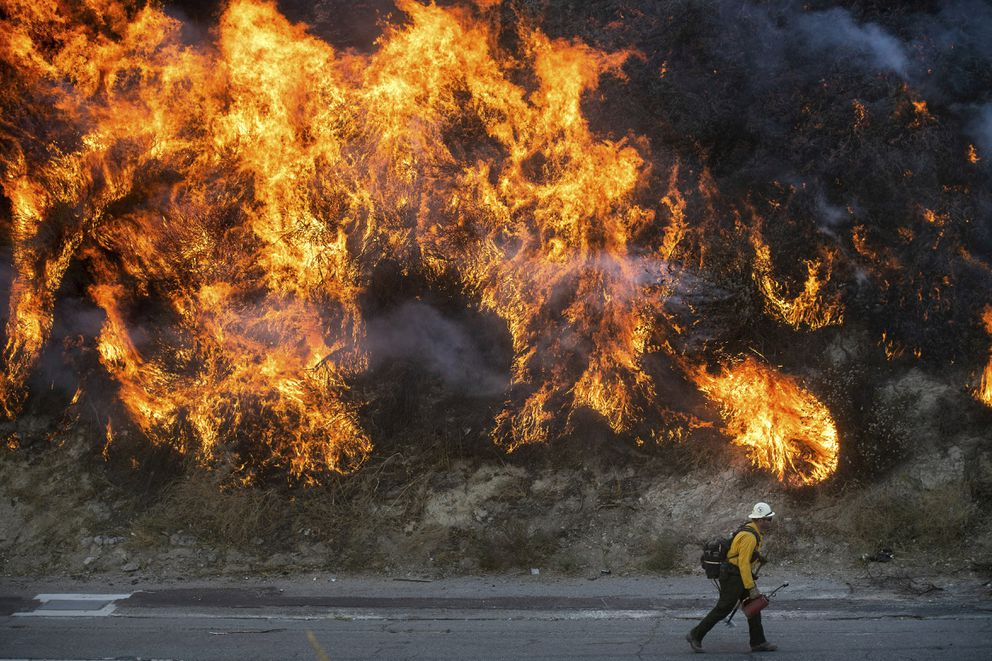 Flames from a backfire, lit by firefighters to stop the Saddleridge Fire from spreading, burn a hillside in Newhall, Calif., on Friday, Oct. 11, 2019. (AP Photo/Noah Berger)