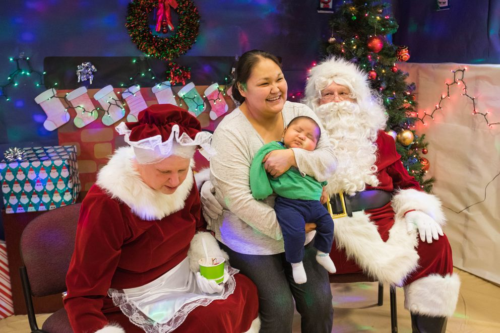 Darlene Chiskok and her 3-month-old son Carl Otten visit with Santa and Mrs. Claus at the Anthony A. Andrews school gym in St. Michael on Tuesday. The humanitarian program, now in its 61st year, brings holiday cheer, books and presents to two rural Alaska communities each year. (Loren Holmes / ADN)