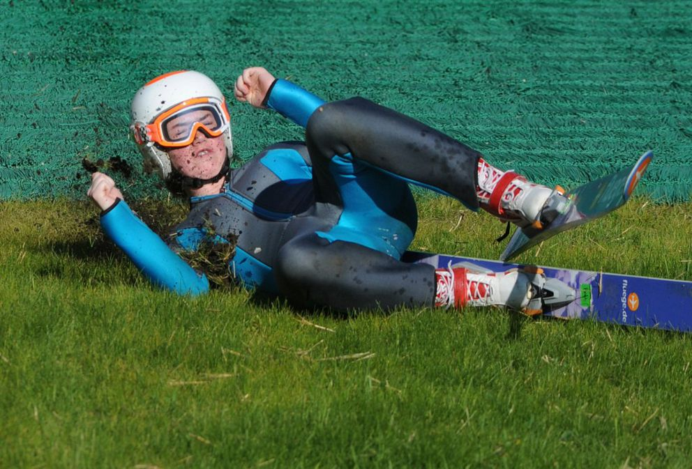 Bret Congdon, 16, slides through the grass as she practiced jumping on the 20-meter hill during an 80-degree evening at the recently upgraded Karl Eid Ski Jumping Complex at Hilltop Ski Area in Anchorage on Thursday. Jumpers can now train and compete year-round with water-coated steel tracks and plastic grass that simulate slippery snow. (Bill Roth / Alaska Dispatch News)
