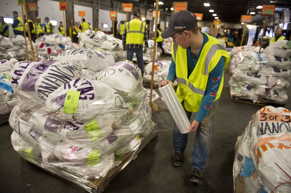Jacob Hubbard, one of dozens of missionary volunteers for The Church of Jesus Christ of Latter-day Saints, wraps a pallet bound for Kaltag. (Marc Lester / ADN)