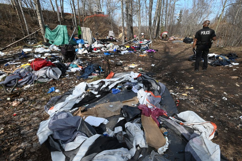 APD Officer Damon Jackson informed people at an illegal homeless camp at Third Avenue and Ingra Street on Thursday, April 30, 2020, that they should clear out before the camp is abated in 10 days. (Bill Roth / ADN)