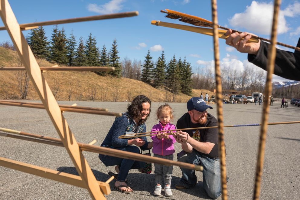 Lucy Rogers, left, helps her niece Ella Robinson, 2, throw an atlatl as Travis Shinabarger points the spear toward a target. (Loren Holmes / Alaska Dispatch News)