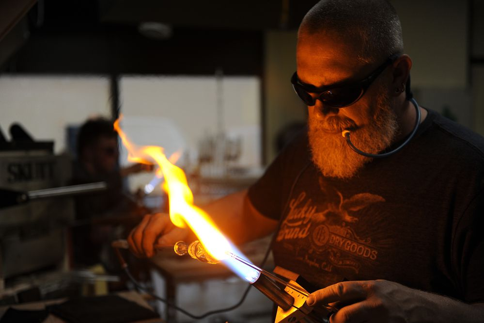 Glass blower Kevin Twing, of Igloo Glass, works on a shot glass at Flowstate Glass Works Studio in Anchorage, Alaska on Wednesday, Sept. 13, 2017. (Bob Hallinen / Alaska Dispatch News)