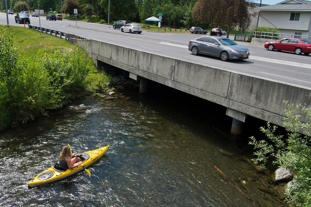 Two kayakers float through a residential neighborhood east of the Seward Highway on Campbell Creek on July 5, 2018. (Marc Lester / ADN)