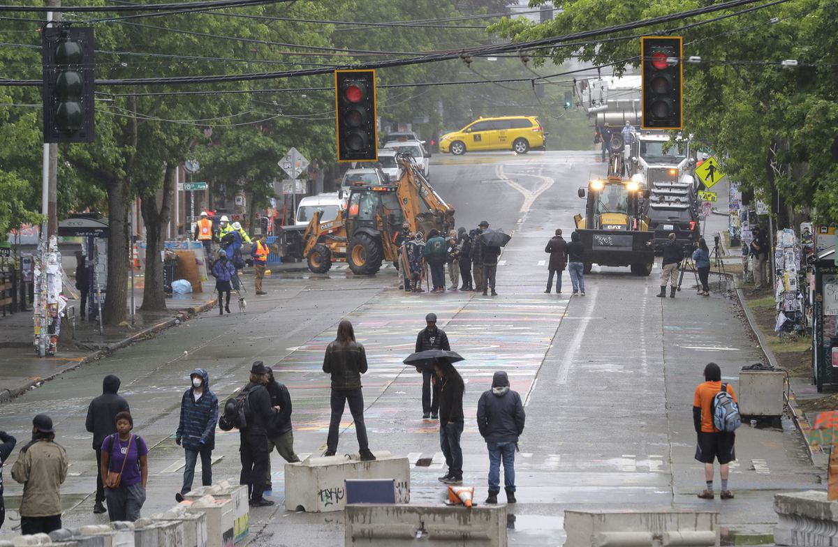 Protesters stand on barricades a block away as Seattle Department of Transportation workers remove other barricades at the intersection of 10th Ave. and Pine St., Tuesday, June 30, 2020 at the CHOP (Capitol Hill Occupied Protest) zone in Seattle. Protesters quickly moved couches, trash cans and other materials in to replace the cleared barricades. The area has been occupied by protesters since Seattle Police pulled back from their East Precinct building following violent clashes with demonstrators earlier in the month. (AP Photo/Ted S. Warren)