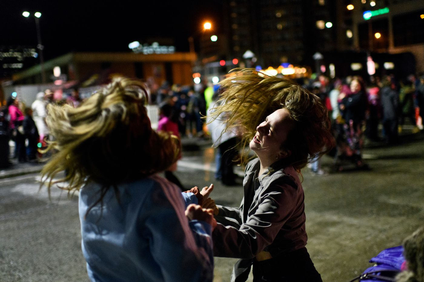 Annie Couey, left, and Gillian Skidmore dance while a rock band plays. (Marc Lester / ADN)