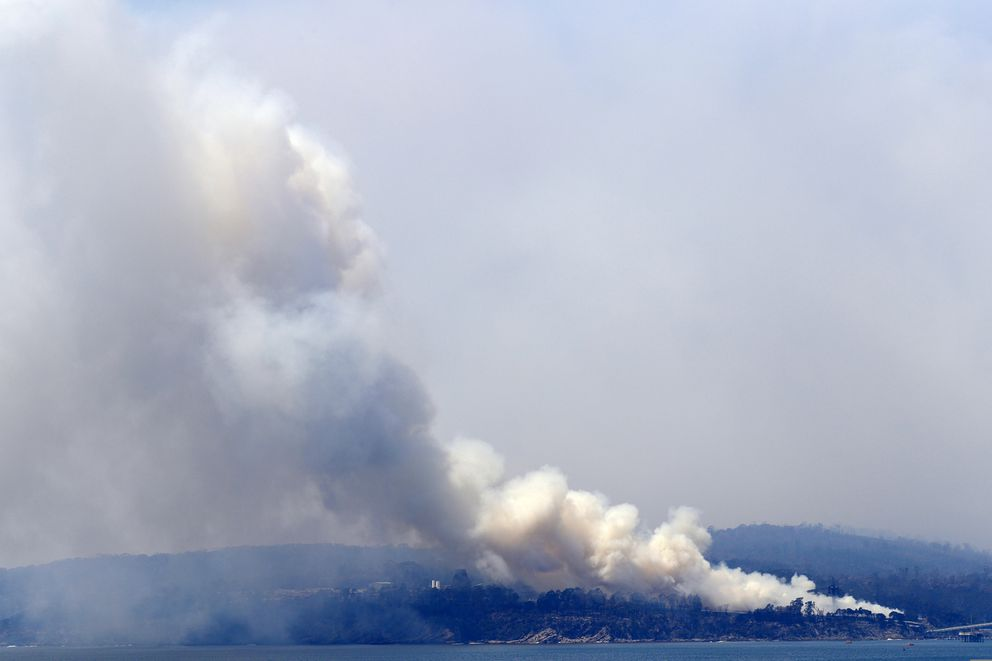 A plume of smoke rises from a fire in a huge wood chip pile at a mill in Eden, Australia, Saturday, Jan. 11, 2020, after catching alight where nearby wildfires sparked the blaze. (AP Photo/Rick Rycroft)