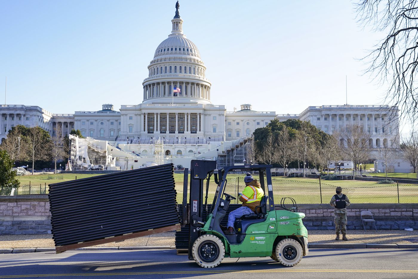 DC National Guard stands outside a mostly quiet Capitol, Thursday morning, Jan. 7, 2021 in Washington, as workers place security fencing in place. (AP Photo/John Minchillo)