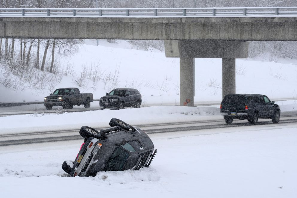 An overturned vehicle awaits assistance at the JBER-Fort Richardson overpass on Wednesday morning along the Glenn Highway. (Erik Hill / Alaska Dispatch News)