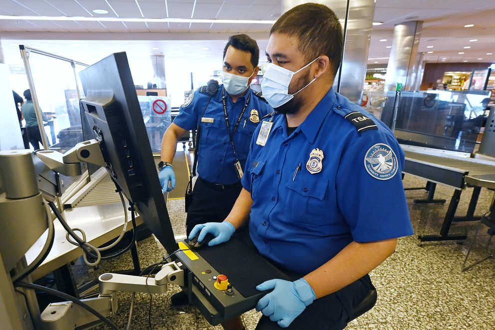 Transportation Security Officers Daylon Brown, left, and Jacob Cachola operate a computed tomography (CT) scanner while screening travelers' carry-on luggage at the TSA security screening in the Ted Stevens Anchorage International Airport on Monday. (Bill Roth / ADN)