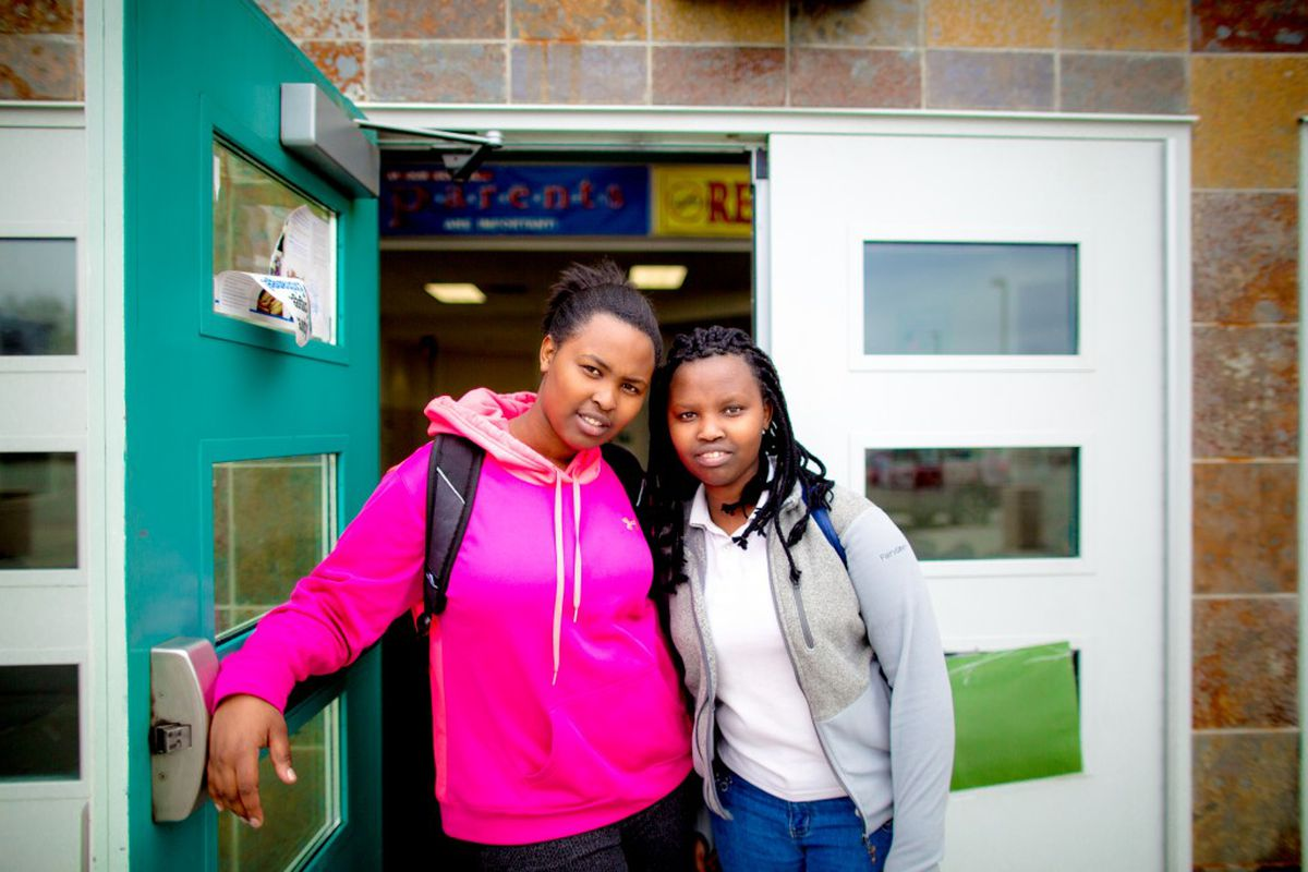 Florence Mbabazi and her younger sister Denise Bamurange stand at the main entrance of Wendler Middle School. They are both students at the Newcomers' Center.(Aymann Ismail / Slate.com)