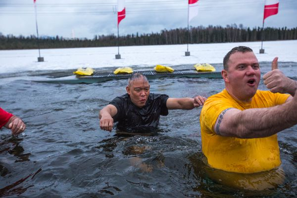Deputy state fire marshal Lloyd Nakano, left, and Alaska State Trooper Capt. Andrew Merrill test the waters at Goose Lake on Friday, Dec. 15, 2017. Special Olympics Alaska will hold its annual Polar Plunge fundraiser Saturday. (Loren Holmes / ADN)