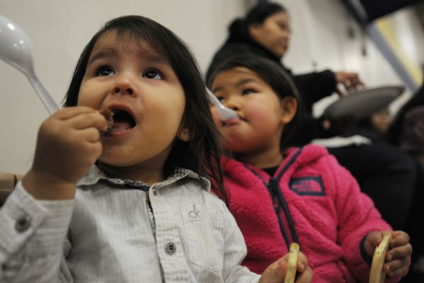 Lucian Maillelle, 1, eats a piece of moose meat while seated next to his cousin Delinda Maillelle, 3, during a Southcentral style welcome potlatch at the Moseley Sports Center on the APU campus on Sunday, Oct. 14, 2018. (Bill Roth / ADN)