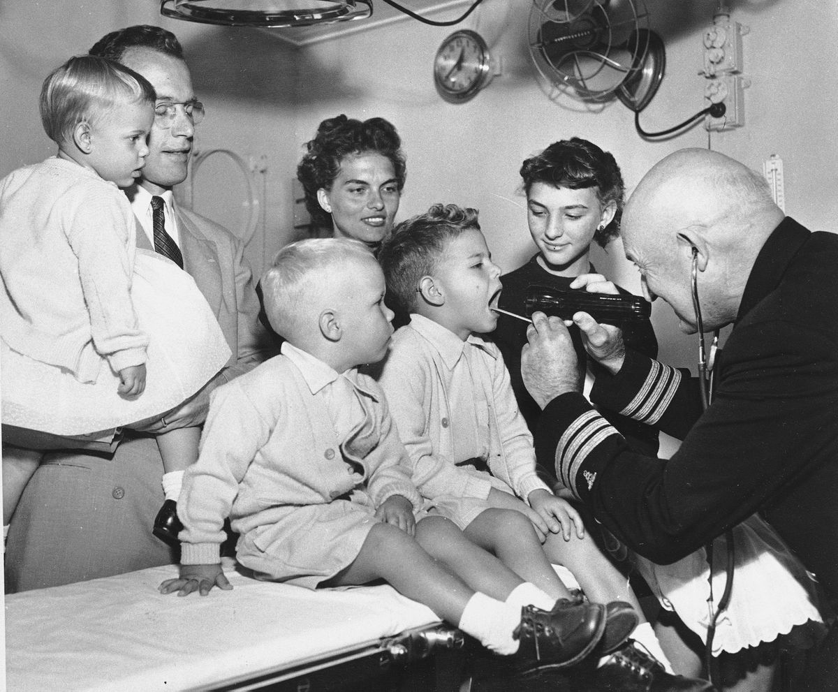 Dr. Francis D. Galbraith, ship's surgeon aboard the liner President Cleveland, checks the Eugene Reynolds family of Chicago for any sign of the Asiatic flu before they disembark, June 9, 1957, in San Francisco. The liner, with 500 passengers aboard, was delayed two hours in docking while the U.S. Public Health SErvice officials interviewed those who have recovered from the malady while aboard the ship (AP Photo)