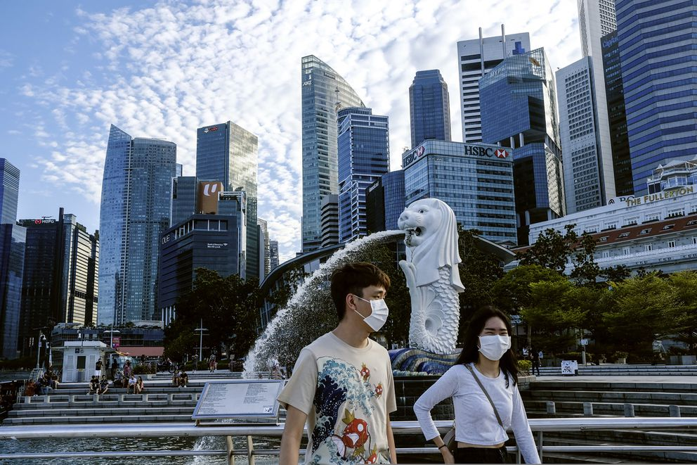 FILE - In this March 14, 2020, photo, a couple wearing face masks walk past the Merlion statue in Singapore. A second wave of coronavirus infections in tightly packed foreign workers' dormitories has caught Singapore off guard, and exposed the danger of overlooking marginal groups in a health crisis. Infections in Singapore, an affluent Southeast Asian city-state of fewer than 6 million people, have jumped more than a hundredfold in two months — from 226 in mid-March to over 23,000, the most in Asia after China and India. (AP Photo/Ee Ming Toh, File)