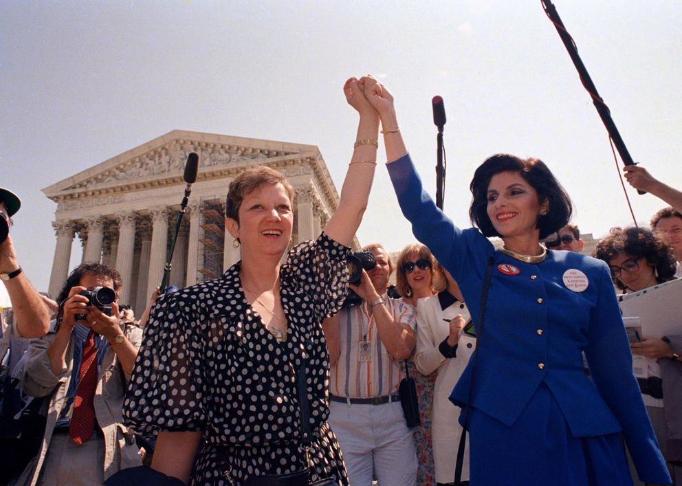 In this April 26, 1989, photo, Norma McCorvey, Jane Roe in the 1973 court case, left, and her attorney Gloria Allred hold hands as they leave the Supreme Court building in Washington after sitting in while the court listened to arguments in a Missouri abortion case. (AP Photo/J. Scott Applewhite, File)