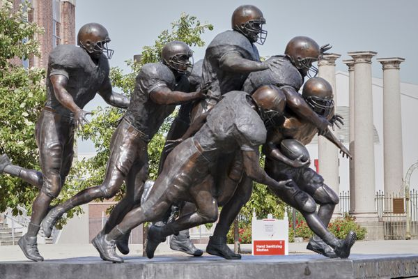 A hand sanitizing station is placed behind a statue of football players outside Memorial Stadium in Lincoln, Neb., Tuesday, Sept. 15, 2020. (AP Photo/Nati Harnik)