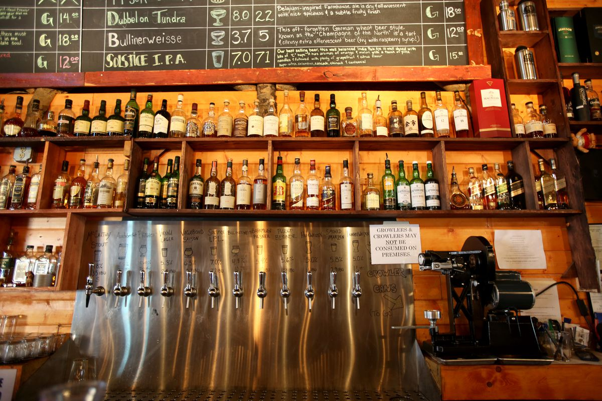 Beer taps and whiskey bottles line the back of the bar at 49th State Brewing Co. (Shelby Lum / ADN)