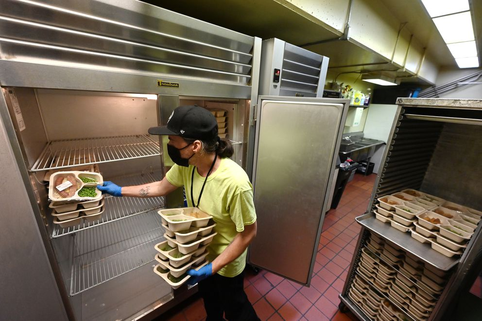 Chris Amaro transfers Meals On Demand produced by Bean's Cafe to serve homeless clients at the shelter. Amaro, a former client, is working in food services through the Shelter to Success program. 'I like what I do, ' said Amaro. 'I like helping people out. ' (Bill Roth / ADN)